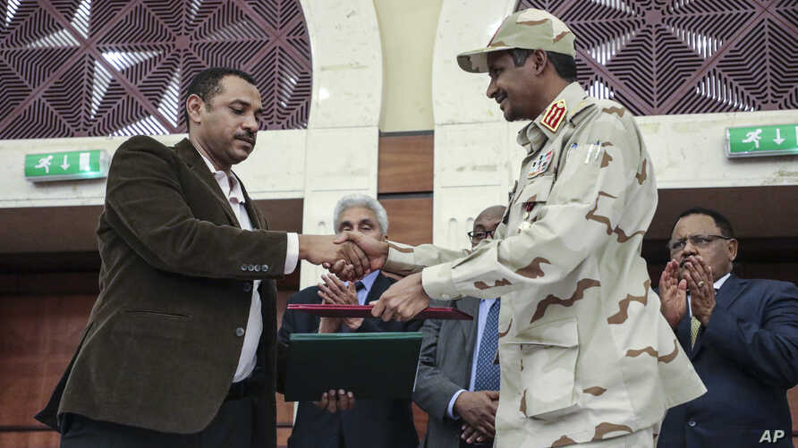 Gen. Mohammed Hamdan Dagalo, right, and Sudan's pro-democracy movement leader Ahmad al-Rabiah shake hands after signing a power sharing document in Khartoum, Sudan, Wednesday, July 17, 2019. The two sides are still at work on a more contentious…