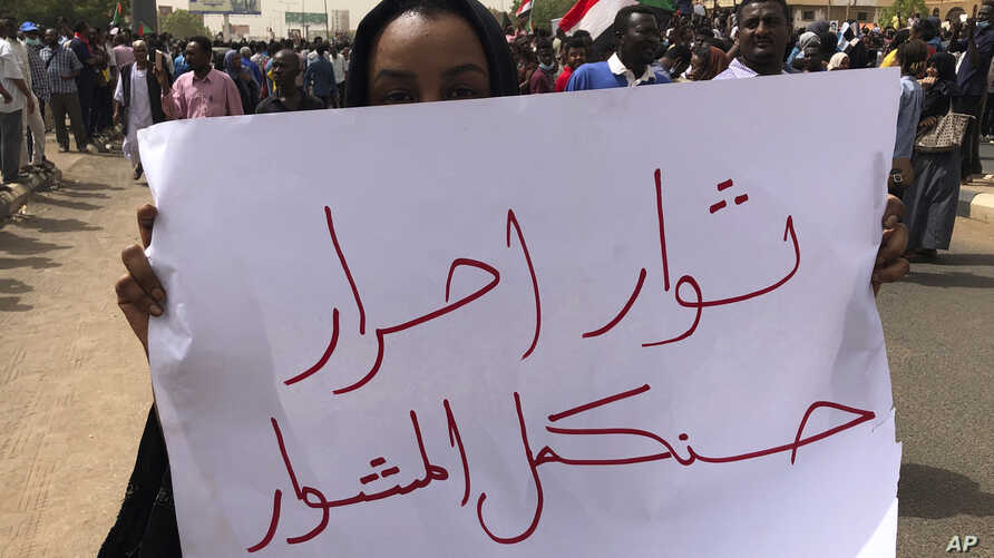 "A Sudanese protester holds an Arabic placard that reads: ""Free revolutionaries will continue the path,"" during a demonstration against the military council, in Khartoum, Sudan, Sunday, June 30, 2019. Tens of thousands of protesters have taken to the…"