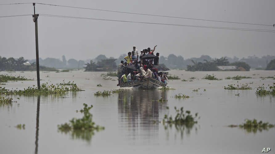 Flood-affected villagers travel on a boat in Gagalmari, in the northeastern Indian state of Assam,  July 19, 2019. In the Indian state of Assam, officials said floodwaters have killed more than a dozen people and brought misery to 4.5 million.