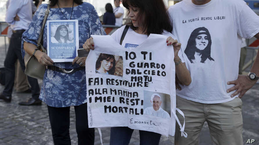 Reanta Grattani, who claims to be a friend of the Orlandi family, center, holds a t-shirt with the pictures of Emanuela Orlandi and Pope Francis and a writing reading: I'm watching you from the sky, but you (referring to Pope Francis) please let…
