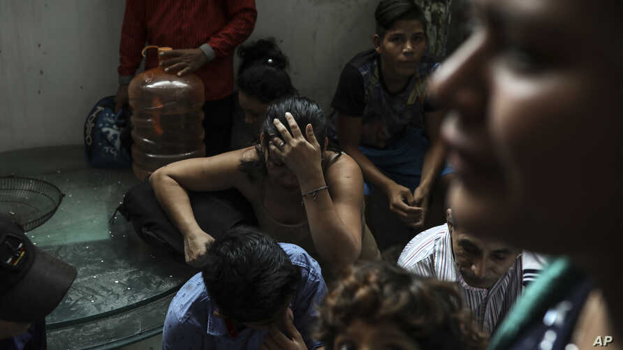 Detained migrants stand together in a storage room at the back of the Azteca Hotel where they tried to hide from  Mexican immigration agents conducting a raid in Veracruz, Mexico,  June 27, 2019.