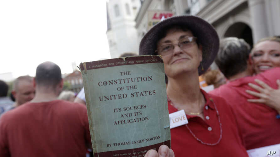 Melanie Miranda, of New Orleans holds a copy of the U.S. Constitution during a celebration rally in Jackson Square in New Orleans, after two Supreme Court decisions supporting gay rights were handed down today, Wednesday, June 26, 2013. (AP Photo…