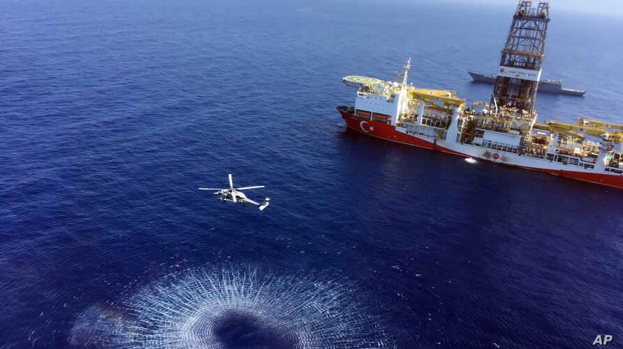 In this Tuesday, July 9, 2019 photo, a helicopter flies near Turkey's drilling ship, 'Fatih' dispatched towards the eastern Mediterranean, near Cyprus.