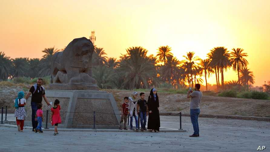 People stand near the Lion of Babylon at the archaeological site of Babylon, Iraq, July 5, 2019. The UNESCO World Heritage Committee named the historic city of Babylon a World Heritage Site.