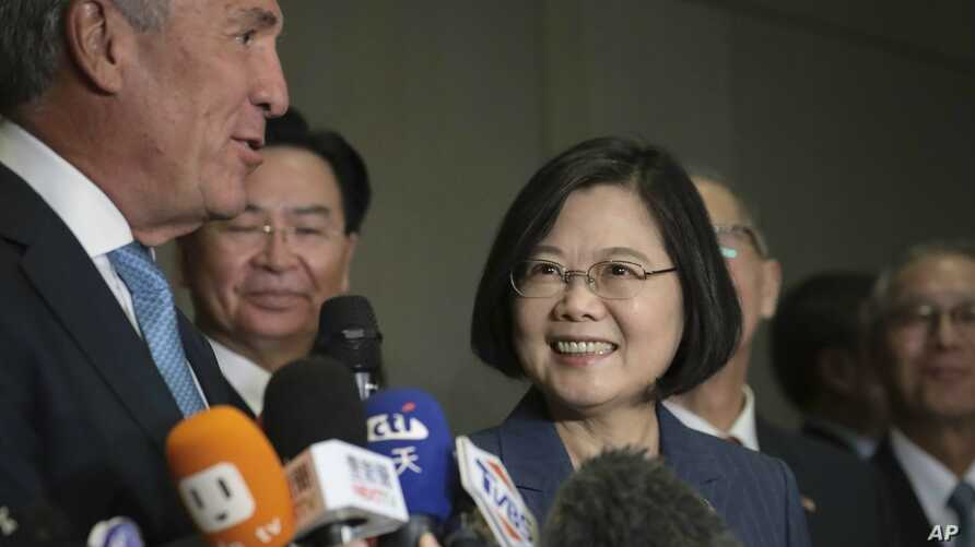 Taiwan President Tsai Ing-wen, center, listens as Michael Splinter, far left, chair of the Taiwan U.S. Chamber of Commerce, speaks to the media at the U.S. Taiwan Business Summit, July 12, 2019, in New York.