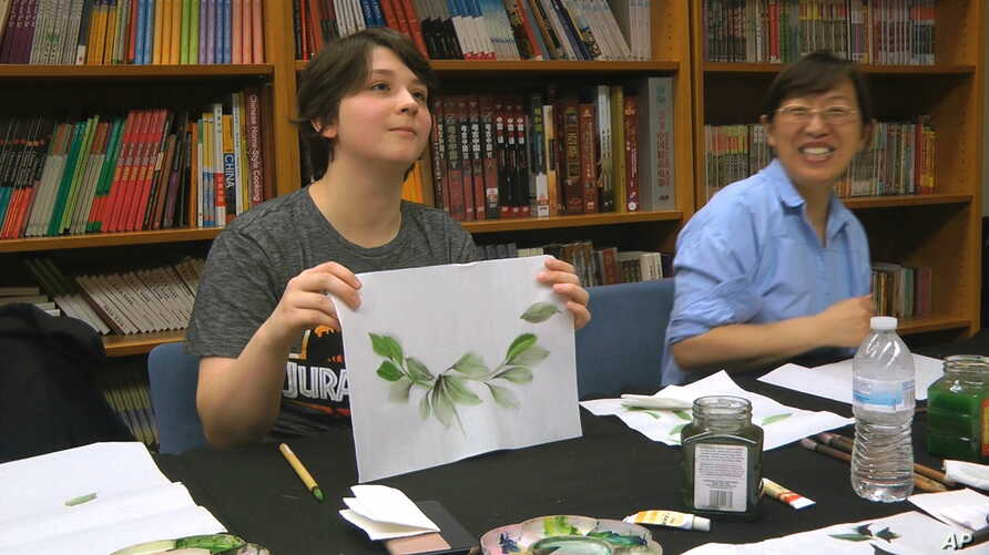 Undergraduate student Moe Lewis, left, shows her watercolor painting of peony leaves at a traditional Chinese painting class at the Confucius Institute at George Mason University in Fairfax, Va., on May 2, 2018. U.S. lawmakers are pushing for…