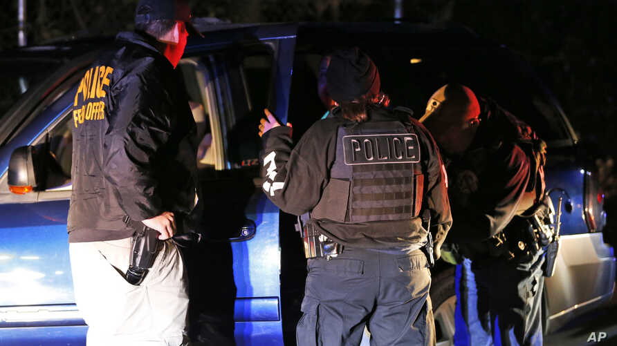 In this Oct. 22, 2018, photo U.S. Immigration and Customs Enforcement agents surround and detain a person during a raid in Richmond, Va. ICE's enforcement and removal operations, like the five-person field office team outside Richmond, hunt people…