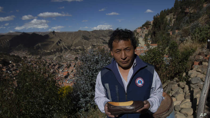 In this June 27, 2019 photo, Abraham Rodríguez poses for a portrait with a finished shoe outside his shoe factory in Villa Rosasani on the outskirts of La Paz, Bolivia. Rodríguez says the tax-free import of goods and the black market have affected…