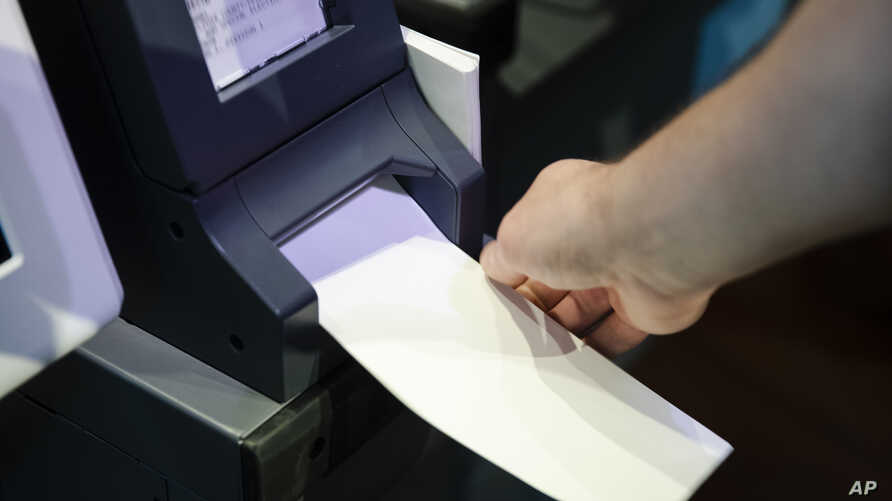 In this June 13, 2019, photo, Steve Marcinkus, an Investigator with the Office of the City Commissioners, demonstrates the ExpressVote XL voting machine at the Reading Terminal Market in Philadelphia. An analysis by The Associated Press has found…