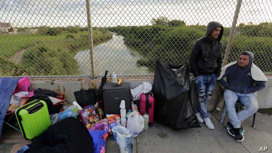 FILE - In this Nov. 2, 2018, file photo, Yenly Morales,left, and Yenly Herrera, right, immigrants from Cuba seeking asylum in the United States, wait on the Brownsville and Matamoros International Bridge in Matamoros, Mexico.