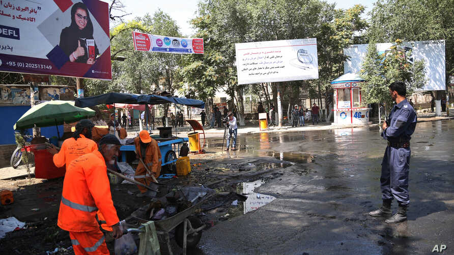 Afghan security forces stand guard near the site of an explosion in Kabul, Afghanistan, July 19, 2019. A powerful bomb exploded outside the gates of Kabul University in the Afghan capital Friday, according to police and health officials.