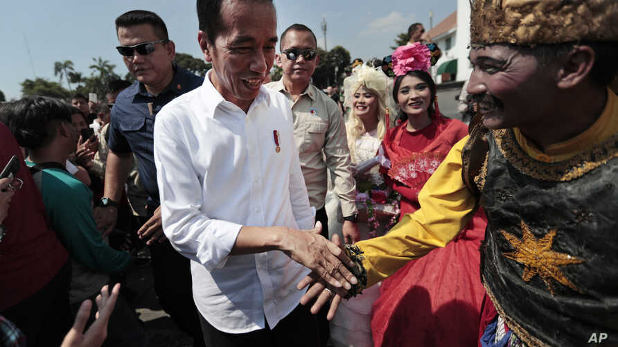 Indonesian President Joko Widodo, center, is greeted by a street busker during his visit at the Old Town in Jakarta, Indonesia, Friday, 26, 2019. Widodo said he will push ahead with sweeping and potentially unpopular economic reforms.