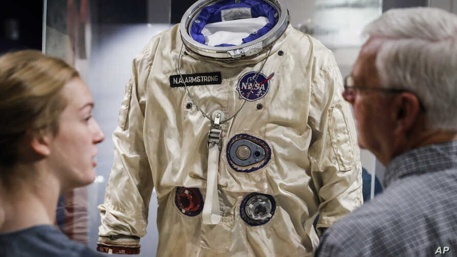 Visitors stand before the spacesuit worm by astronaut Neil Armstrong that was used on his Gemini VIII mission at the Armstrong Air & Space Museum, Wednesday, June 26, 2019, in Wapakoneta, Ohio.  Neil Armstrong helped put Wapakoneta  on the map July…