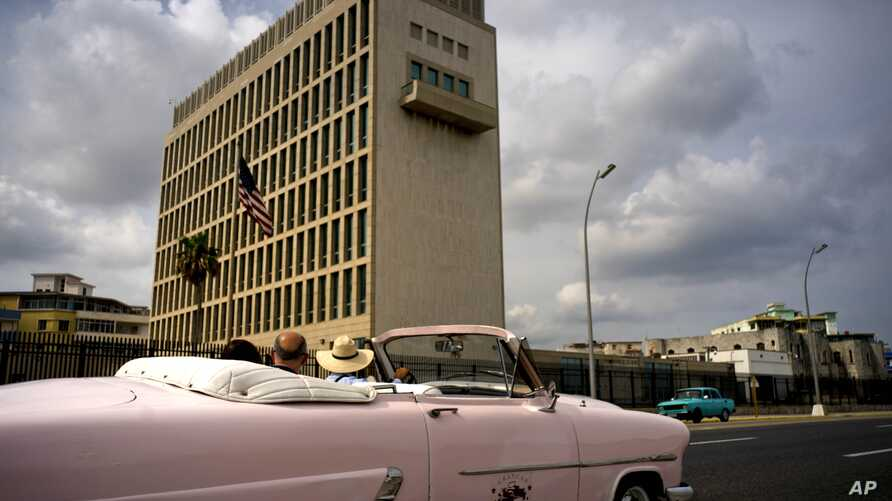 Tourists take a  ride in a vintage car as they pass the U.S. embassy in Havana, Cuba, March 18, 2019.