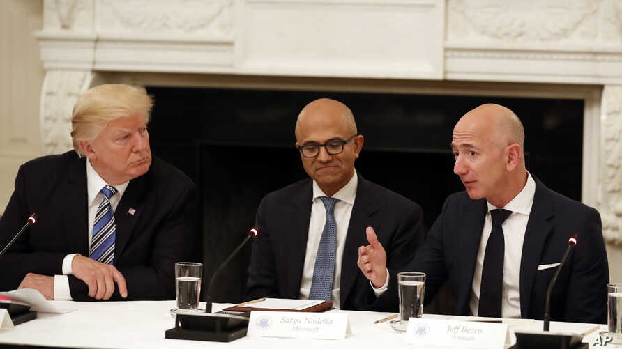 FILE - In this June 19, 2017, file photo President Donald Trump, left, and Satya Nadella, Chief Executive Officer of Microsoft, center, listen as Jeff Bezos, Chief Executive Officer of Amazon, speaks during an American Technology Council roundtable…