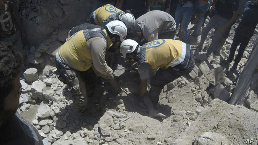 This photo provided by the Syrian Civil Defense White Helmets, which has been authenticated based on its contents and other AP reporting, shows Syrian White Helmet civil defense workers pull out a victim from under the rubble of a destroyed building…