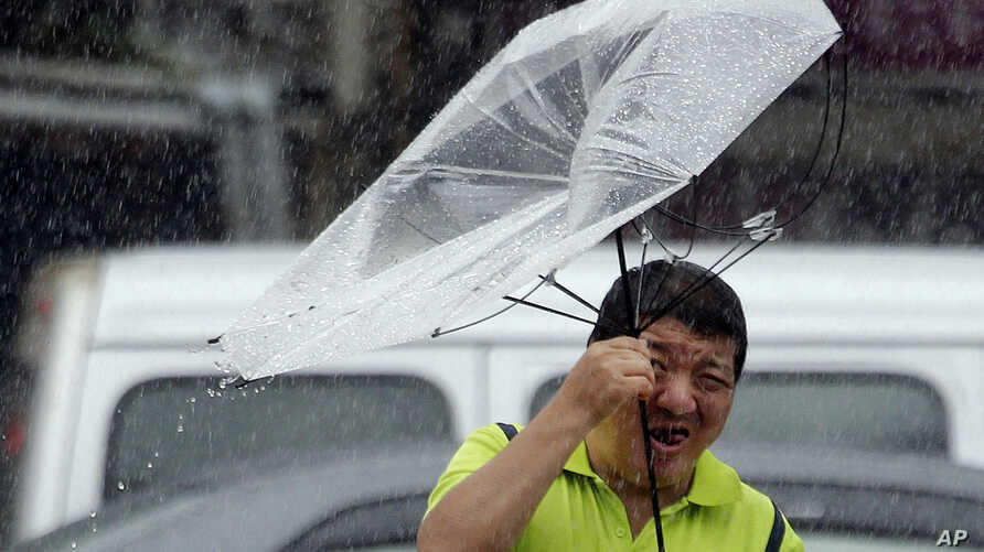 A Taiwanese man holds an umbrella against powerful gusts of wind generated by typhoon Lekima in Taipei, Taiwan, Friday, Aug. 9, 2019. (AP Photo/Chiang Ying-ying)