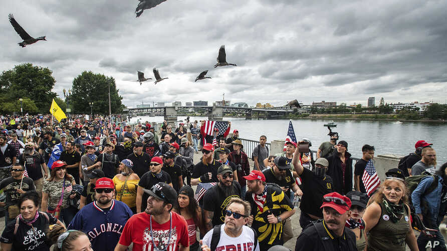 "Members of the Proud Boys and other right-wing demonstrators march along the Willamette River during an ""End Domestic Terrorism"" rally in Portland, Ore., on Saturday, Aug. 17, 2019. Police have mobilized to prevent clashes between conservative…"