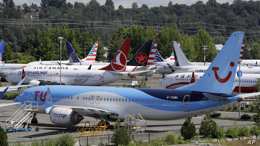 Dozens of grounded Boeing 737 MAX airplanes crowd a parking area adjacent to Boeing Field Thursday, Aug. 15, 2019, in Seattle. Aviation authorities around the world grounded the plane in March after two fatal crashes. (AP Photo/Elaine Thompson)