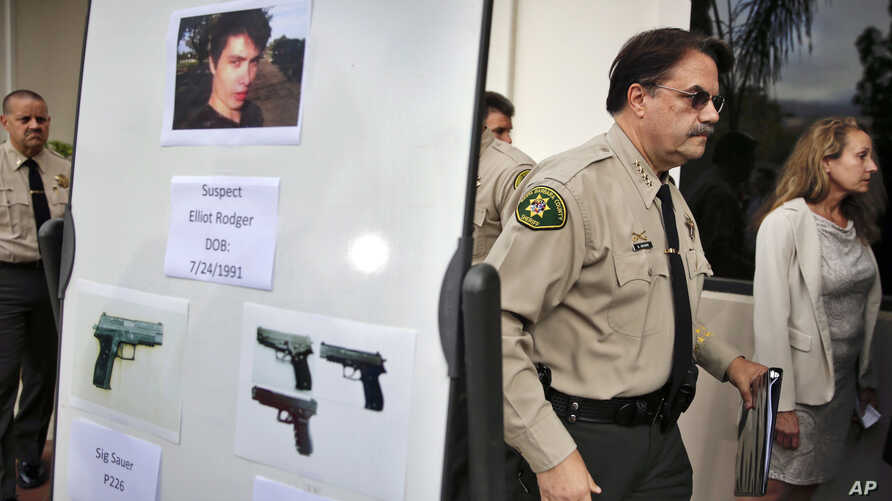 FILE - In this May 24, 2014 file photo, Santa Barbara County Sheriff Bill Brown, right, walks past a board displaying photos of gunman Elliot Rodger and the weapons he used in a mass shooting in Isla Vista, Calif., after a news conference in Santa…