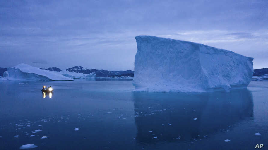 FILE - In this Aug. 15, 2019, file photo, a boat navigates at night next to large icebergs in eastern Greenland. As warmer temperatures cause the ice to retreat the Arctic region is taking on new geopolitical and economic importance, and not just…