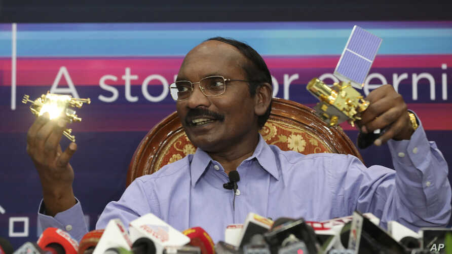 Indian Space Research Organization (ISRO) Chairman Kailasavadivoo Sivan displays a model of Chanrayaan 2 orbiter and rover during a press conference at their headquarters in Bangalore, India, Aug. 20, 2019.