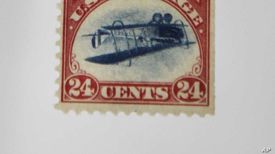 "This June 5, 2009, photo shows a famous 1918 ""inverted Jenny"" stamp featuring an upside-down biplane being held by Charles Shreve, president of Spink Shreves Galleries, in his office in Dallas."