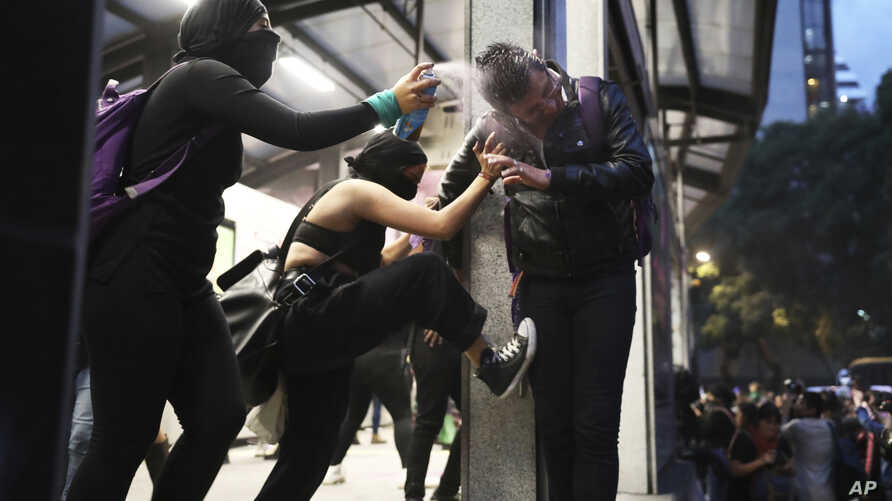 Two women assault a commuter, one spraying him in the face with paint another kicking him, at a bus station, during a protest sparked by a string of alleged sexual attacks by police officers, in Mexico City, Friday, Aug. 16, 2019. On Friday,…