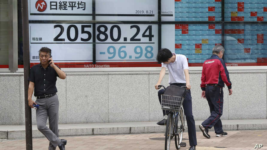 People stand by an electronic stock board of a securities firm in Tokyo, Wednesday, Aug. 21, 2019. Asia stock markets followed Wall Street lower Wednesday as investors looked ahead to a speech by the Federal Reserve chairman for signs of possible…