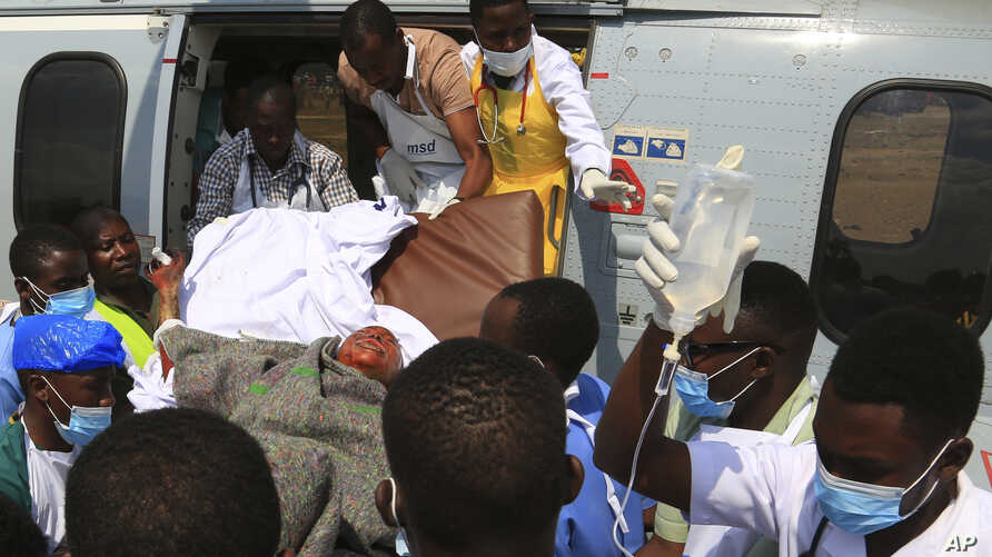 Health workers carry a wounded Tanzanian from a military helicopter at Jangwani grounds in Dar es Salaam, Tanzania, Aug. 11, 2019.