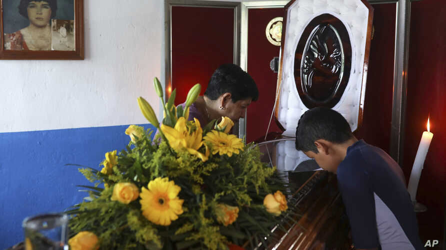 Twelve-year-old Jesus Ruiz stands before the coffin containing the remains of his father, Mexican journalist Jorge Celestino Ruiz Vazquez, in Actopan, Veracruz, Aug. 3, 2019. The state attorney's office said Ruiz Vazquez was found dead at his home Friday.