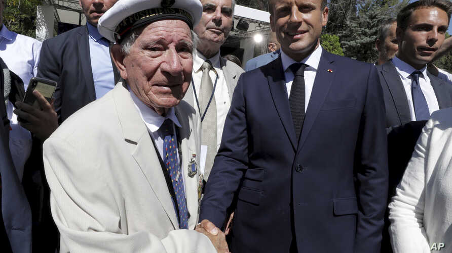 French President Emmanuel Macron shakes hands to a veteran during a ceremony marking the 75th anniversary of the WWII Allied landings in Provence, in Saint-Raphael, southern France, Thursday, Aug. 15, 2019.