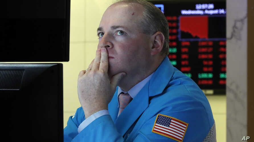 Specialist Edward Loggie works on the floor of the New York Stock Exchange, Aug. 14, 2019. Stocks are falling sharply after the bond market threw up another warning flag on the economy.