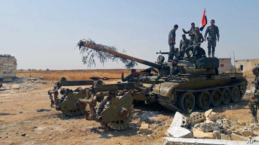 In this Aug. 13, 2019 photo, released by the Syrian official news agency SANA, Syrian army soldiers flash the victory sign as they stand on a tank, in northwestern Syria.