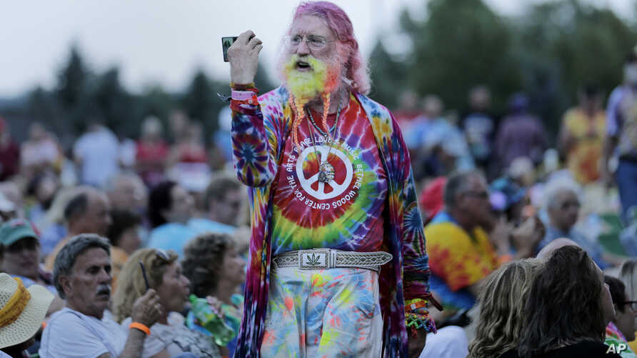 A man walks through the crowd during an Arlo Guthrie concert at a Woodstock 50th anniversary event in Bethel, N.Y., Aug. 15, 2019. Woodstock fans are expected to get back to the garden to mark the 50th anniversary of the generation-defining festival.