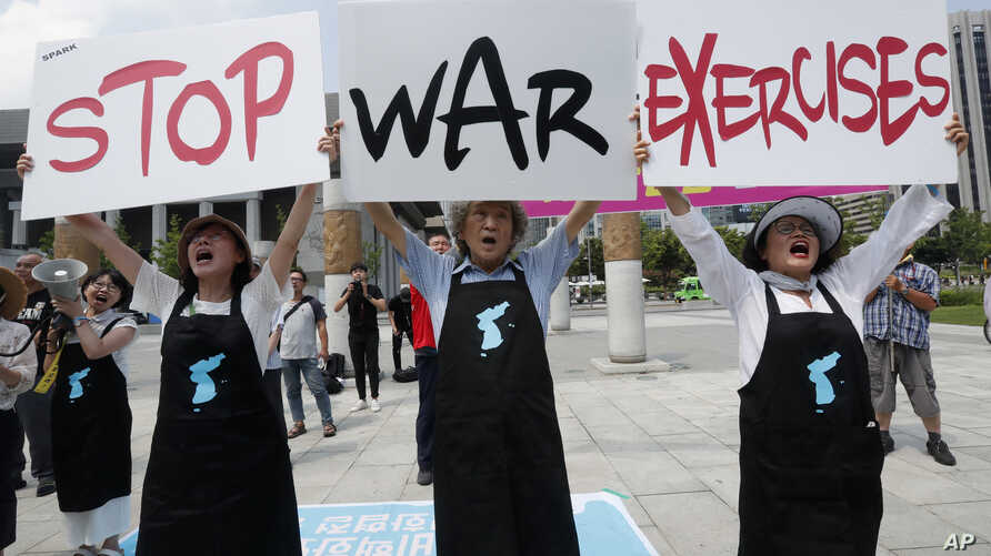 Protesters shout slogans while holding signs to oppose planned joint military exercises between South Korea and the United States near the U.S. embassy in Seoul, South Korea, Aug. 5, 2019.