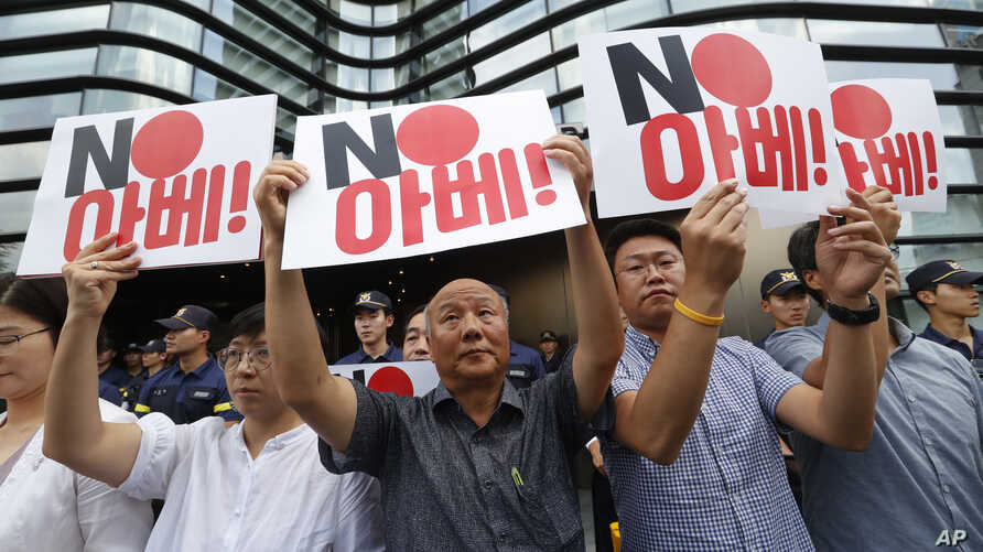 "South Korean protesters hold up cards during a rally against Japan in front of a building that houses the Japanese embassy in Seoul, South Korea, Aug. 2, 2019.  The signs read "" Japanese Prime Minister Shinzo Abe."""