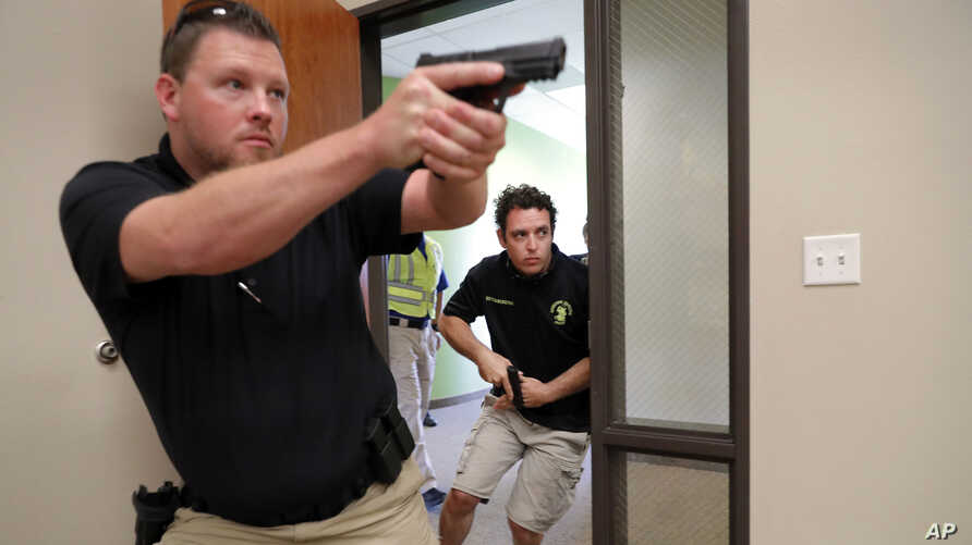 Trainees Chris Graves, left, and Bryan Hetherington, right, participate in a security training session at Fellowship of the Parks campus in Haslet, Texas, July 21, 2019.