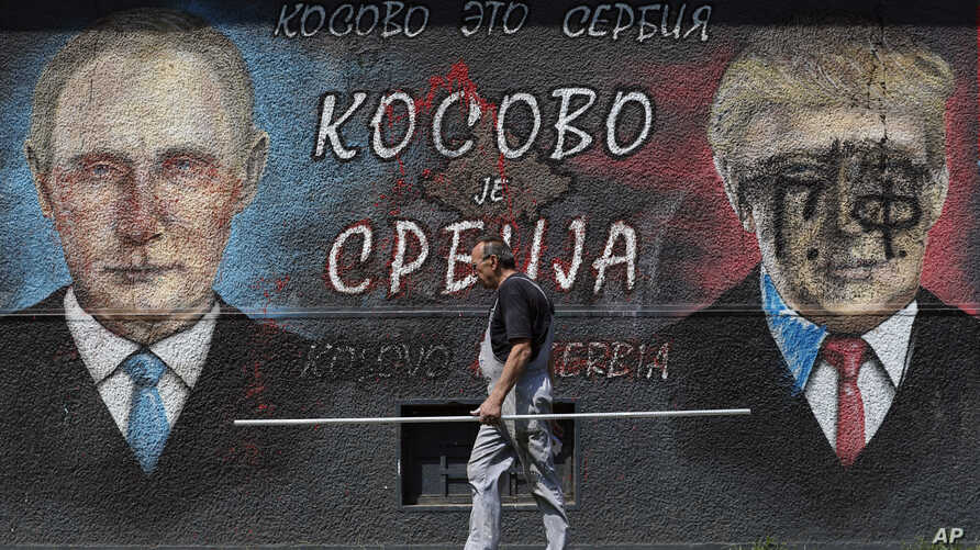 "A man passes by graffiti depicting the Russian President Vladimir Putin, left, and US President Donald Trump in Belgrade, Serbia, Friday, Aug. 9, 2019. The Cyrillic letters on graffiti read ""Kosovo is Serbia"". A former Serbian province, Kosovo…"