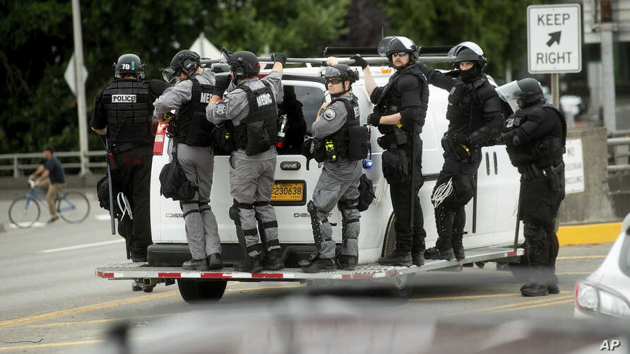 "Police officers ride on the side of a van as right-wing demonstrators and counter-protesters gather in Portland, Ore., for an ""End Domestic Terrorism"" rally on Saturday, Aug. 17, 2019.  Police seized metal poles, bear spray and other weapons as…"
