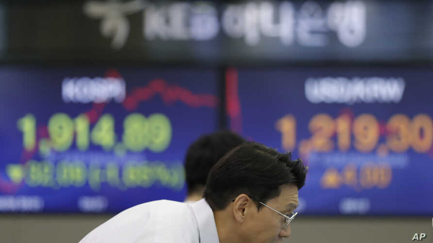 A currency trader watches the computer monitors near the screens showing the Korea Composite Stock Price Index (KOSPI), left, and the foreign exchange rate between U.S. dollar and South Korean won at the foreign exchange dealing room in Seoul, South…