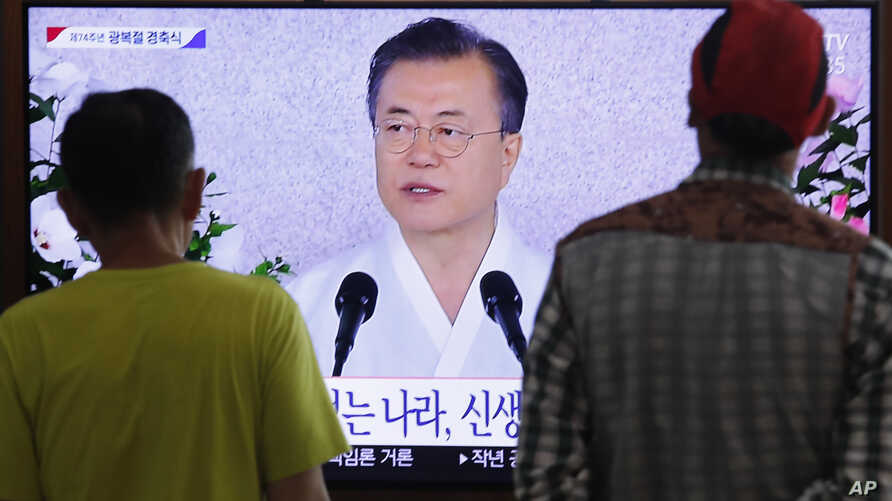 People watch a TV screen showing a live broadcast of South Korean President Moon Jae-in's speech during a ceremony to celebrate the Korean Liberation Day, marking the 74th anniversary of Korea's liberation from the Japanese colonial rule, at the…