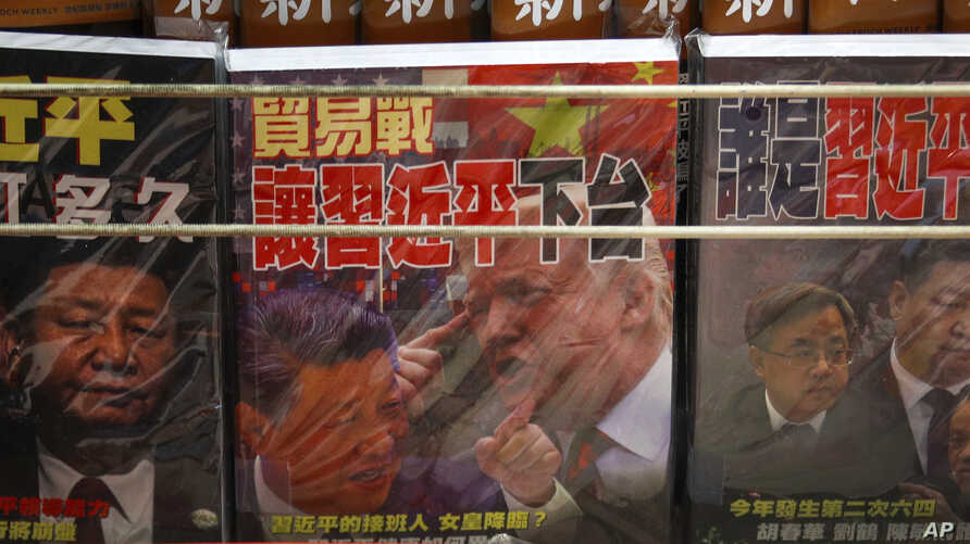 FILE - In this July 4, 2019, file photo, magazines with a front cover featuring Chinese President Xi Jinping and U.S. President Donald Trump on trade war is placed on sale at a roadside bookstand in Hong Kong. China has announced some U.S…