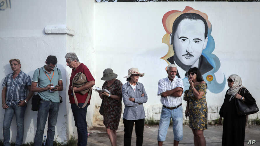 Voters queue outside a polling station during the first round of the presidential election, in La Marsa, outside Tunis, Tunisia, Sunday Sept. 15, 2019. Tunisia is holding a cacophonous presidential election this weekend, with voters choosing among…