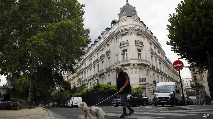 A man walks his dog next to an apartment building owned by Jeffrey Epstein in the 16th district in Paris, Tuesday, Aug. 13, 2019.