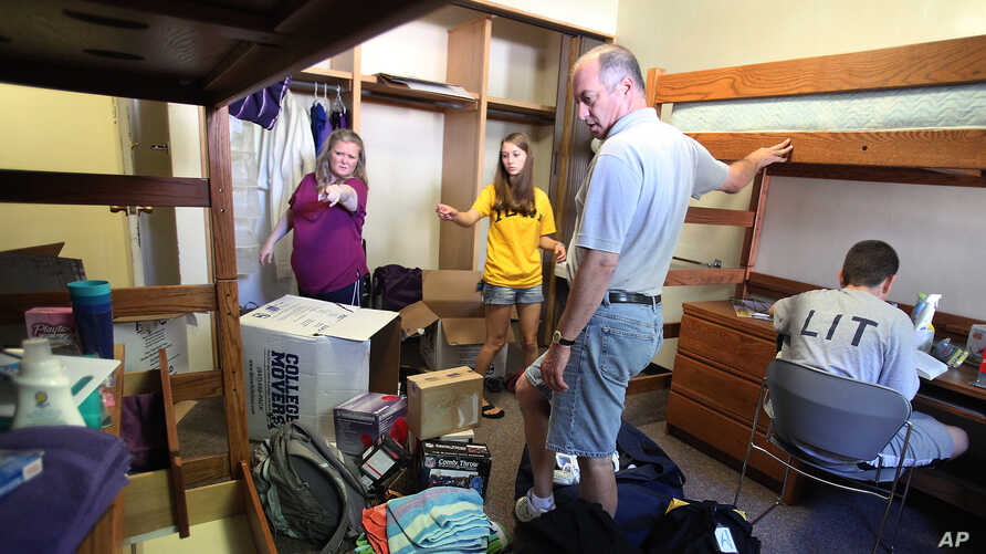 In this Aug. 16, 2010 photo, Paul and Robin Kramer from Chicago help their daughter Ariana move into her dormitory room on the campus of the University of Iowa in Iowa City.  Ariana, 18, is one of many college freshmen who are saying goodbye to…