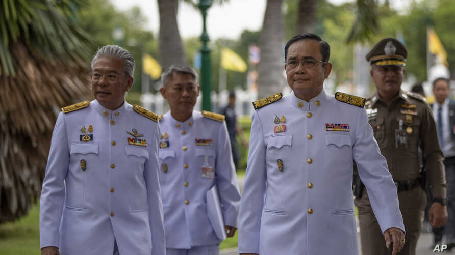 Thailand Prime Minister Prayuth Chan-ocha, second right walks to attend a cabinet meeting with aides and at the Government House of Thailand in Bangkok, Thailand, Tuesday, Aug. 27, 2019.  Prayuth Chan-ocha omitted a sentence in the oath of office…