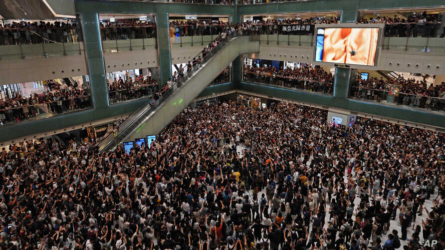 """Local residents sing a theme song written by protesters """"Glory be to thee"""" at a shopping mall in Hong Kong Wednesday, Sept. 11, 2019. Hong Kong Chief Executive Carrie Lam reassured foreign investors Wednesday that the Asian financial hub can rebound…"""