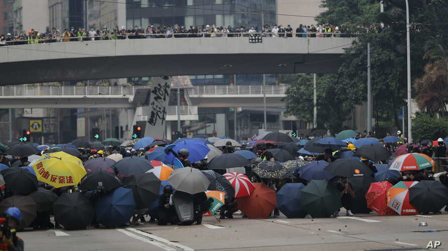 Protestors shield behind umbrellas as they prepare to face off with police in Hong Kong, Sunday, Sept. 29, 2019. Riot police fired tear gas Sunday after a large crowd of protesters at a Hong Kong shopping district ignored warnings to disperse in a…
