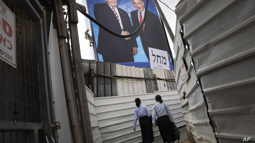 Two women walk through an alley past an election campaign billboard of the Likud party shows Israeli Prime Minister Benjamin Netanyahu, right, and US President Donald Trump in Bnei Brak, Israel, Sunday, Sept 8, 2019. (AP Photo/Oded Balilty)